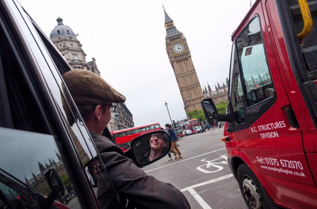 Photograph of Robet Lordan driving a black cab in London.